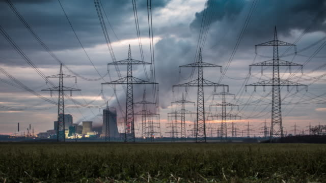 time lapse: electrical pylons in front of a power station - tracking shot - уголь стоковые видео и кадры b-roll
