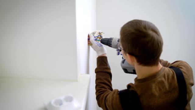 vídeos y material grabado en eventos de stock de técnico electricista conecta un mecanismo de toma de corriente a los cables en una pared blanca, usando un atornillador - brigada
