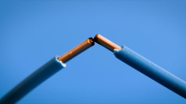 vídeos y material grabado en eventos de stock de cables eléctricos chispas sobre fondo azul - descarga eléctrica