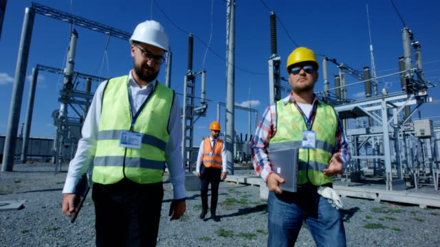 electrical workers walking outside - centrale elettrica video stock e b–roll