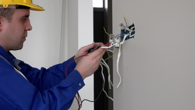 Electrician checking socket voltage using multimeter in a wall fixture socket video
