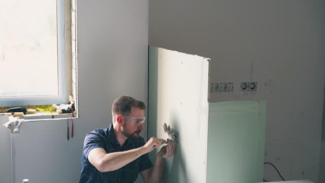 vídeos de stock e filmes b-roll de electrician fixes plug on wall using screwdriver in room - obras em casa janelas