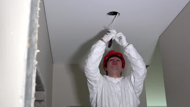 Electrician installing electrical cables wires on new building ceiling video