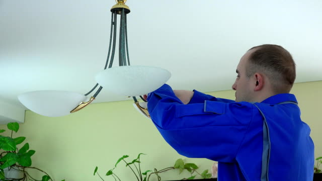 electrician man climb up and change light bulb to economic one. video