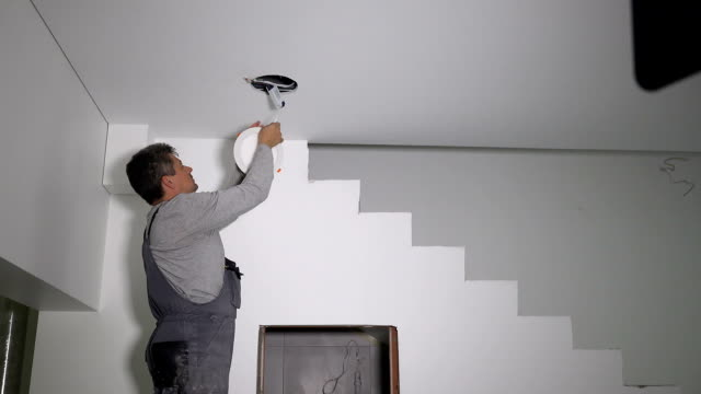 vídeos de stock e filmes b-roll de electrician man connect wire and install led light lamp into ceiling hole - led painel