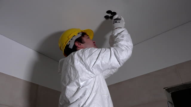 Electrician man with handsaw cutting hole in ceiling for lighting installation video