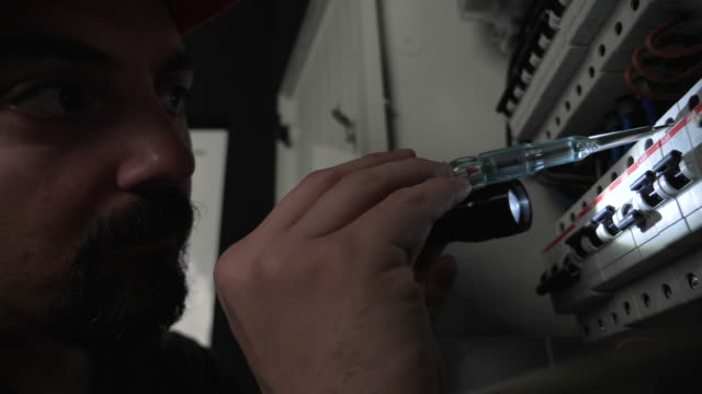 Electrician repair fuse box, use flashlight Electrician repair fuse box, use flashlight. Footage is taken in studio environment with Panasonic GH5 camera futebol stock videos & royalty-free footage