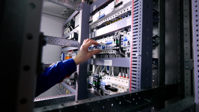 Electrician switching off electrical power, pushing switches in eletrical cabinets. video