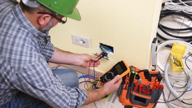vídeos de stock, filmes e b-roll de técnico do eletricista no trabalho em um sistema elétrico residencial. indústria da construção civil. - eletricista