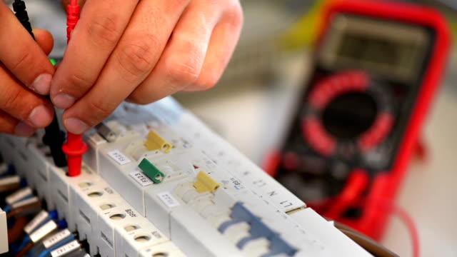 vídeos de stock, filmes e b-roll de eletricista testando um painel elétrico inteligente - eletricista