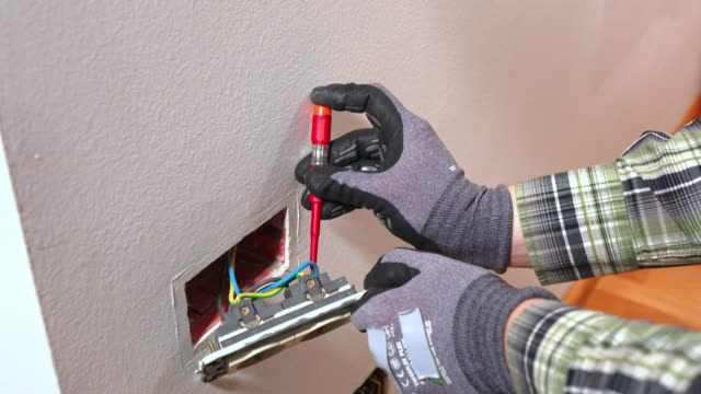 Electrician using a screwdriver, working on electrical wiring video