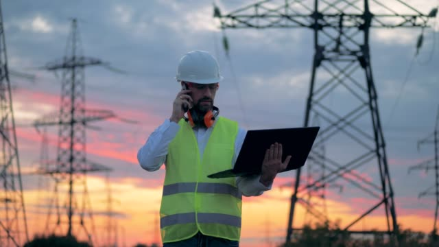 Electrician using cell phone near at the power line, electrical substation. 4K.