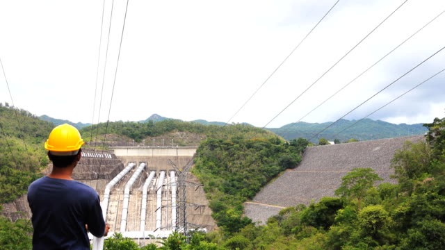 Electricity Engineer man on the phone at dam.