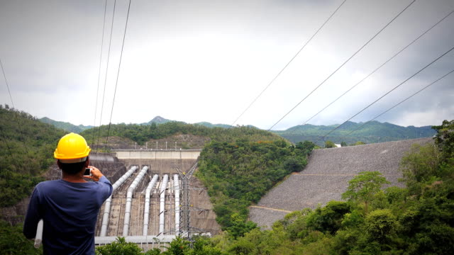 Electricity Engineer man on the phone at dam. video