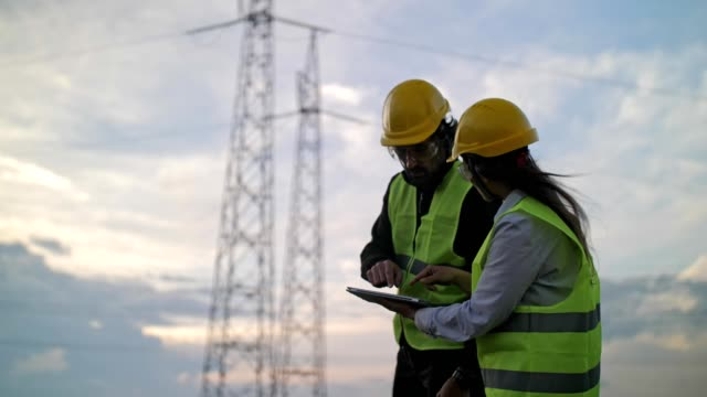 Electricity Engineers working on the field near a High Voltage Line with a Clear Blue Sky and Sun Rays behind them. Electrical engineers working on Electrical Pylons Translation, discussing the condition of the Electrical Power Pole, Technology, Power Equipment, Global Business, Electrical Equipment power stock videos & royalty-free footage