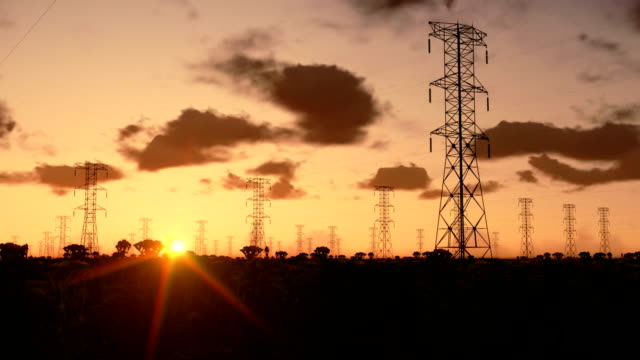 Electricity pillars at sunrise Electricity pillars at sunrise high voltage sign stock videos & royalty-free footage