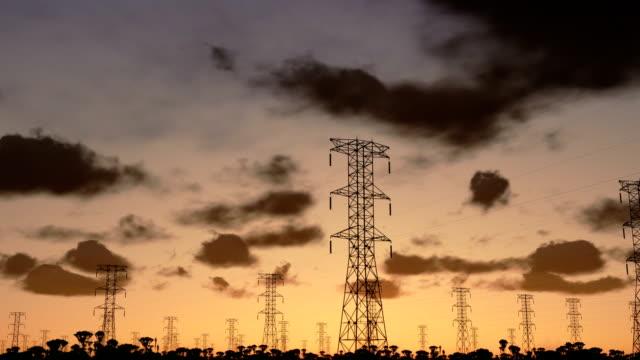 электричество колонны, замедленная съемка sunrise, camera панорамирование - lightning стоковые видео и кадры b-roll