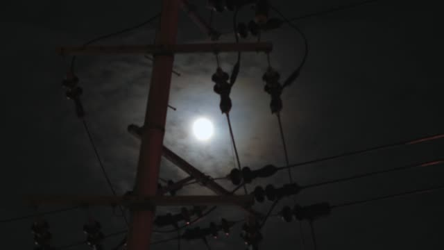 Electricity pole and wire at moving clouds over the moon in timelapse view video