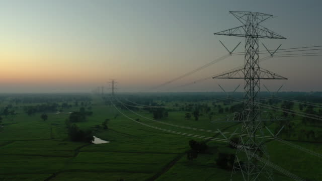 Electricity pylons dolly shot 4k aerial view real time of electricity pylons in the rural scene with sunrise, Power line and Prosperity concept, Development and growth for the city high voltage sign stock videos & royalty-free footage