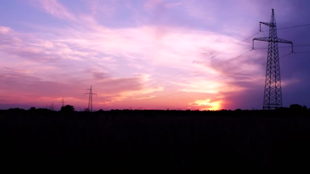 Electricity transmission towers on sunset background. Time lapse