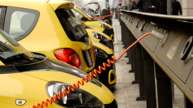 Electro car is charging in the street Small yellow electro cars is charging in the street station. Close-up. power supply stock videos & royalty-free footage