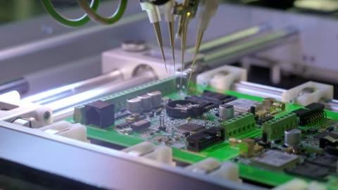 elektronische leiterplattenproduktion. automatisierte circut board maschine produziert gedruckte digitale elektronische platine. elektronik-auftragsfertigung. herstellung von elektronischen chips. hightech - herstellendes gewerbe stock-videos und b-roll-filmmaterial