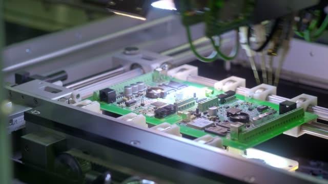 電子回路基板の生産。自動サーカットボードマシンは、印刷されたデジタル電子ボードを生成します。エレクトロニクス受託製造。電子チップの製造ハイテク - 半導体点の映像素材/bロール