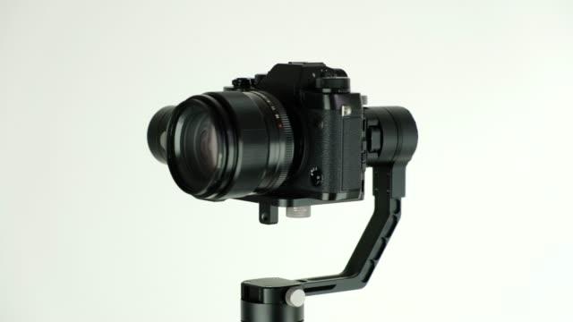 デジタルカメラが白い背景に回転する電子定常カメラ - スタビライザー使用点の映像素材/bロール