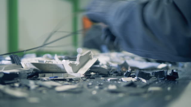Electronics' debris are being arranged while moving along the belt
