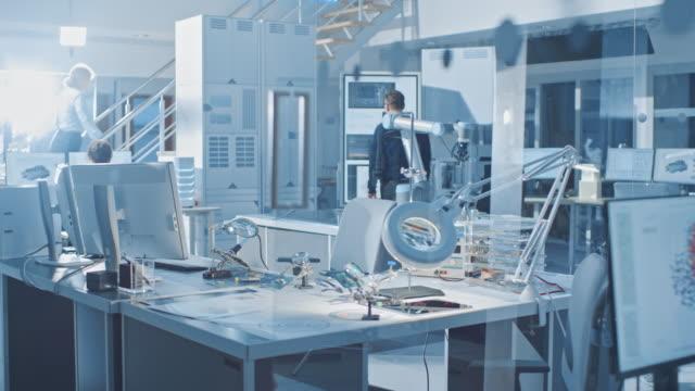 elektronik design engineer tar hans plats börjar arbeta med kretskort, gör underhåll och lödning moder kort komponenter. skärmen visar neurala nätverk, maskin inlärning, cloud computing - datorstödd tillverkning bildbanksvideor och videomaterial från bakom kulisserna