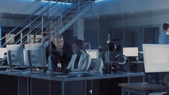 vidéos et rushes de ingénieur de développement électronique travaillant sur ordinateur, entretiens avec le chef de projet. l'équipe des professionnels utilisent l'apprentissage machine et les réseaux neuronaux forr le design moderne d'ingénierie industiral. - science et technologie