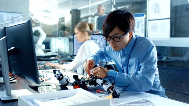 電子工学のエンジニアは、ロボット、電圧チェックとプログラムの応答時間で動作します。コンピューター科学研究所で仕事をする専門家。 - 科学研究点の映像素材/bロール
