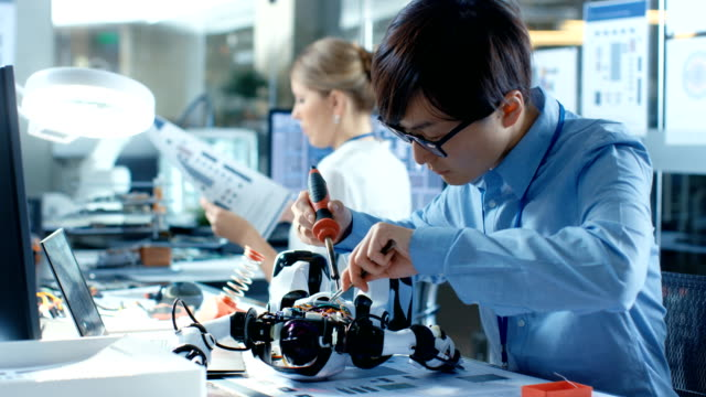 Electronics Engineer Works with Robot, Soldering Wires and Circuits. Computer Science Research Laboratory with Specialists Working.