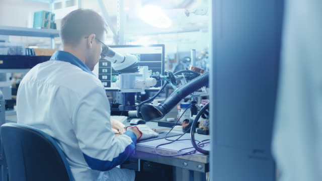 electronics factory worker in white work coat inspects a printed circuit board through a digital microscope. high tech factory facility. - przemysł elektroniczny filmów i materiałów b-roll
