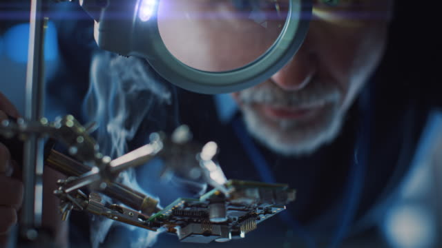 electronics maintenance and repair engineer soldering motherboard, microchip and circuit board, looking through magnifying glass. conceptual shot: close-up low angle magnifying eye and face - цп стоковые видео и кадры b-roll