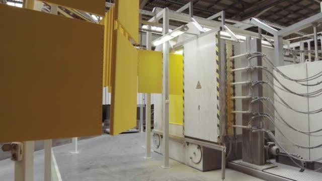 Electrostatic painting. Yellow metal panels move on an overhead conveyor.