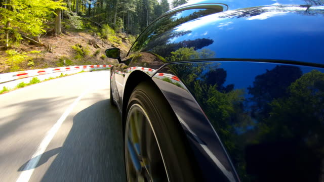 Elegant and luxurious sports car driving on a winding mountain road on a beautiful sunny day Driving an elegant and luxurious blue sports car on an empty country road through picturesque scenery on a beautiful sunny day sports car stock videos & royalty-free footage
