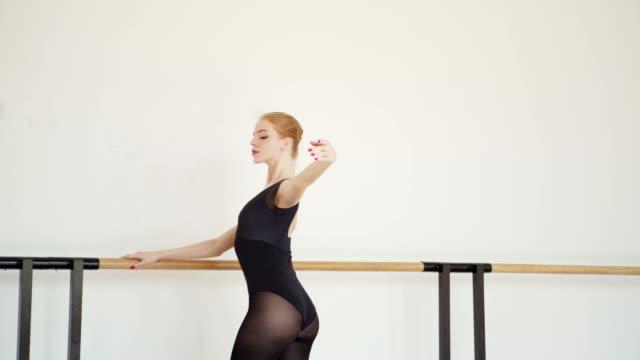 elegant ballerina in black leotard practicing port de bras at barre in ballet dance studio, side view tracking shot - trykot filmów i materiałów b-roll