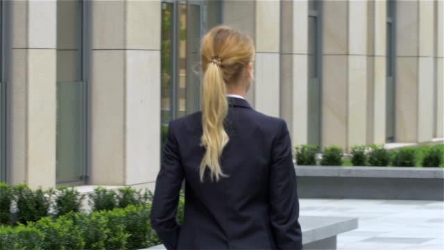 elegant blond affärskvinna med surfplatta går runt kontorsbyggnad. slowmotion - djurarm bildbanksvideor och videomaterial från bakom kulisserna