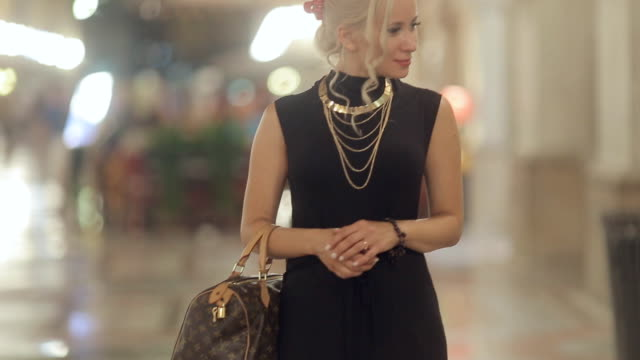 elegant blonde on high heels and dressed in a long black dress consider showcases in milan in the evening - paris fashion stock videos and b-roll footage