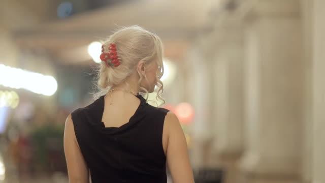 vídeos de stock, filmes e b-roll de elegante loira com salto alto e decorado em um vestido longo preto se apresenta em milão na noite - moda parisiense