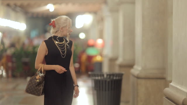 Elegant blonde on high heels and dressed in a long black dress consider showcases in Milan in the evening video