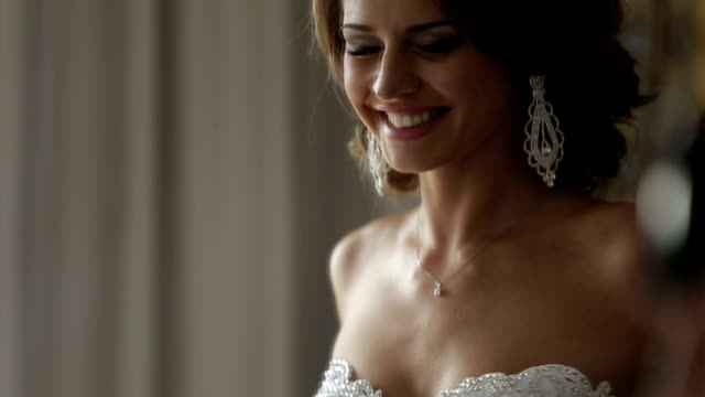 Elegant brunette bride with beautiful earrings and diamond dress getting ready for wedding day video