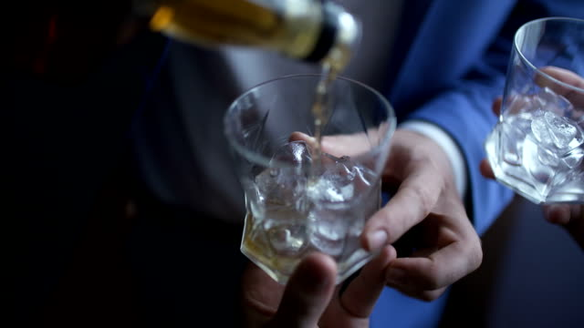 elegant businessman pouring whiskey into glass - rum superalcolico video stock e b–roll