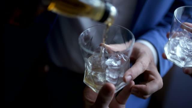 グラスにウイスキーを注ぐ優雅なビジネスマン - 酒場点の映像素材/bロール