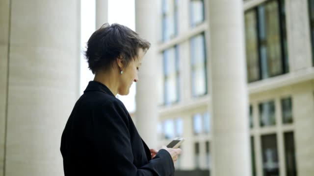 elegant businesswoman standing outdoors next to office building, texr messaging on her cell phone and looking away with dreamy smile, full circle pan - krótkie włosy filmów i materiałów b-roll