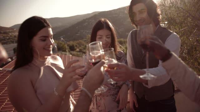 vídeos y material grabado en eventos de stock de amigos elegantes haciendo un brindis en el patio de casa de pueblo mediterráneo - moda de otoño