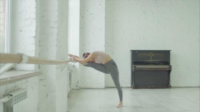 eleganta tjej gör leg stretching motion på barre - balettstång bildbanksvideor och videomaterial från bakom kulisserna