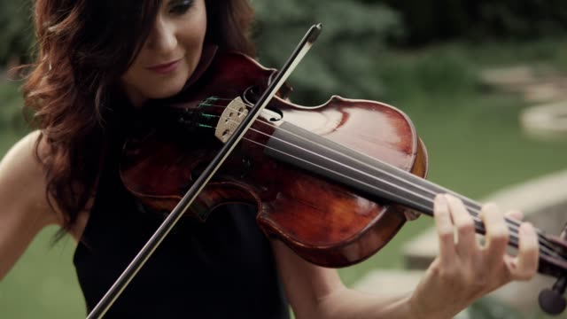 Elegant girl in dress plays violin outdoors. Elegant violinist in forest