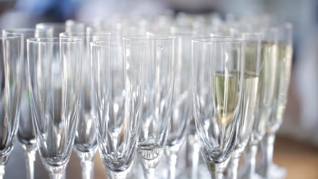 Elegant glasses with champagne standing in a row on serving table during the celebration. Waiters pouring champagne video